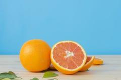 Car pomarańcze na drewnianym stole nad błękitnym tłem Zdjęcie Stock