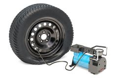 Car portable electric air compressor with puncture car wheel, 3D. Rendering isolated on white background Stock Photos
