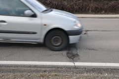 Car and pothole on road Stock Image