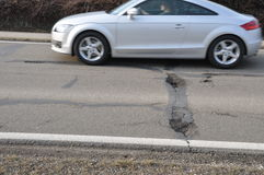 Car and pothole on road. Car passing by potholes on the road Royalty Free Stock Image