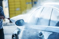 Car Power Cleaning. Men Washing His Car Using Powerful Pressure Washer royalty free stock image