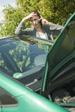 Car problem. Woman with a broken car calling on the cell phone Stock Photos