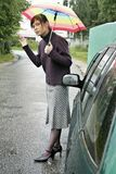 Car problem. Portrait of a young woman with an umbrella, standing by a broken car Stock Images