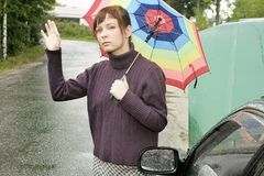 Car problem. Portrait of a young woman with an umbrella, standing by a broken car Stock Photography