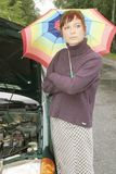Car problem. Portrait of a young woman with an umbrella, standing by a broken car Stock Image
