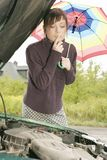 Car problem. Portrait of a young woman with an umbrella, standing by a broken car Royalty Free Stock Photography