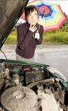 Car problem. Portrait of a young woman with an umbrella, standing by a broken car Royalty Free Stock Photo
