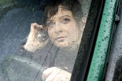 Car problem. Portrait of a young woman, brunette in a car, in a rain-close up Stock Photo