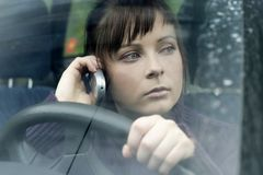 Car problem. Portrait of a young woman, brunette in a car making a phonecall-close up Royalty Free Stock Image