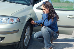 Car problem. Attractive woman with mobile phone and car Royalty Free Stock Image