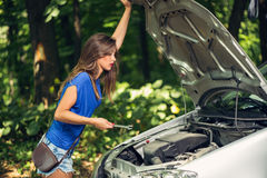 Car Problem. Beautiful young worried woman standing by car that broke down on the road in forest and holding wrench Royalty Free Stock Photography