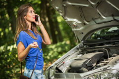 Car Problem. Beautiful young worried woman standing by car that broke down on the road in forest, holding wrench and talking at mobile phone Stock Photo