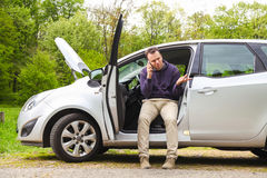 Car problem. Driver is calling service to aid him after car broke on the road Stock Photos