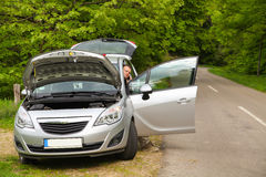 Car problem. Driver is calling service to aid him after car broke on the road Royalty Free Stock Image