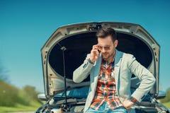 Car problem. Men having problem with car.Calling for insurance assistance Stock Images