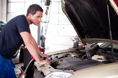 Car Problem. A young mechanic staring at a car, thinking Stock Photo
