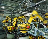 Car production line. Yellow robots welding cars in a production line Royalty Free Stock Photos