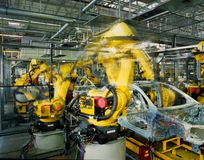 Car production line. Yellow robots welding cars in a production line Stock Images