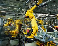 Car production line. Yellow robots welding cars in a production line Stock Photography