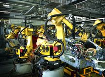 Car production line. Yellow robots welding cars in a production line Stock Image