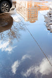 Car and puddle from melting snow in city in spring Royalty Free Stock Image