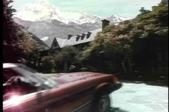 Car pulling up in front of house in snow capped mountains stock video footage