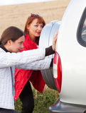 The car is pushed by women Royalty Free Stock Photo