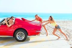 Car pushing teen girls humor funny guy driving. In the beach stock photo