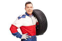 Car racer carrying a tire on his shoulder Royalty Free Stock Photos