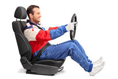 Car racer holding a steering wheel and driving. Profile shot of a young car racer holding a steering wheel and pretending to drive isolated on white background Royalty Free Stock Photo