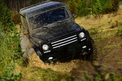 Car racing in autumn forest. Competition, energy and motorsport concept Off road vehicle or SUV overcomes obstacles. Car racing in autumn forest. Competition stock image