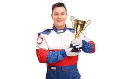 Car racing champion holding a trophy. Young car racing champion holding a gold trophy and looking at the camera isolated on white background royalty free stock photos