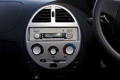 Car Radio and Air Conditioner. A vehicle's center panel. Showing various round dials, for air conditioner adjustment. Also a basic factory fitted radio with mp3 Stock Photos