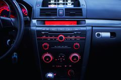 Car radio and air conditioner system. Button on dashboard in modern car panel. Stock Photos