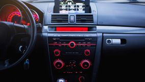 Car radio and air conditioner system. Button on dashboard in modern car panel. Stock Photo