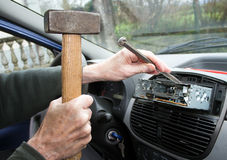 Car radio removal, replacement - amateur at work with hammer and Stock Photos
