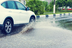 Car rain puddle splashing water Stock Photography