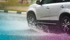 Car rain puddle splashing water. Motion car rain big puddle of water spray from the wheels stock photos