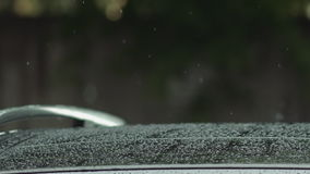 Car in rain with water drops. Rain is dropping on car slowmotion stock footage