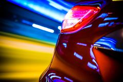 Car Rear Motion Blur. Speeding Modern Car Rear View and Motion Blurred City Lights Stock Image