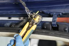 . car. rear trunk lid. wire damage. they are naked very dangerous. electrician eliminates damage with the help of special tools royalty free stock photo