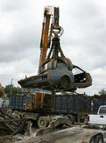 Car Recycling at the Scrap Yard. A 1969 Ford Mustang is picked up by a grappling crane for recycling or crushing Royalty Free Stock Photo
