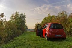 Car is red on a green meadow Stock Photography