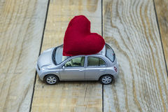 Car with a red heart. On the roof carrying love Royalty Free Stock Photo