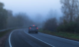 Car with red stoplights on foggy highway. Car with red stoplights goes on empty rural highway in dark autumn foggy morning, blue tonal correction filter effect stock photography