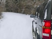 Car With Red Tail Lights. A vehicle rear with tail lights on, winter scene in the blurred background stock photos