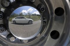 Car Reflection 1. A white car reflected in the shiny hubcap of a truck Royalty Free Stock Image