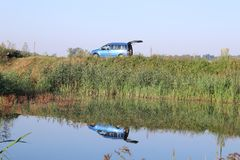 Car reflection in water. Reflection of a blue car in water Stock Photo
