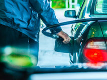 Car refuel fueling at the filling station, holding a fuel pump. Male hand refilling the car with gas or petrol on filling station, holding a fuel pump outdoor Royalty Free Stock Photos