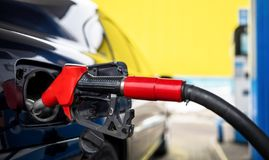 Car refueling on a petrol station closeup. Red fuel nozzle stock image